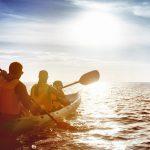 family kayaking on the ocean