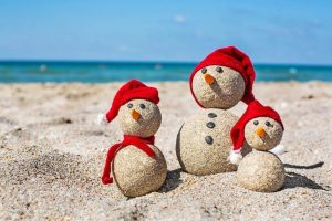 Snowmen made of sand with red hats on the beach