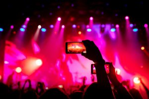 Smartphone in hand at a concert, red light from stage